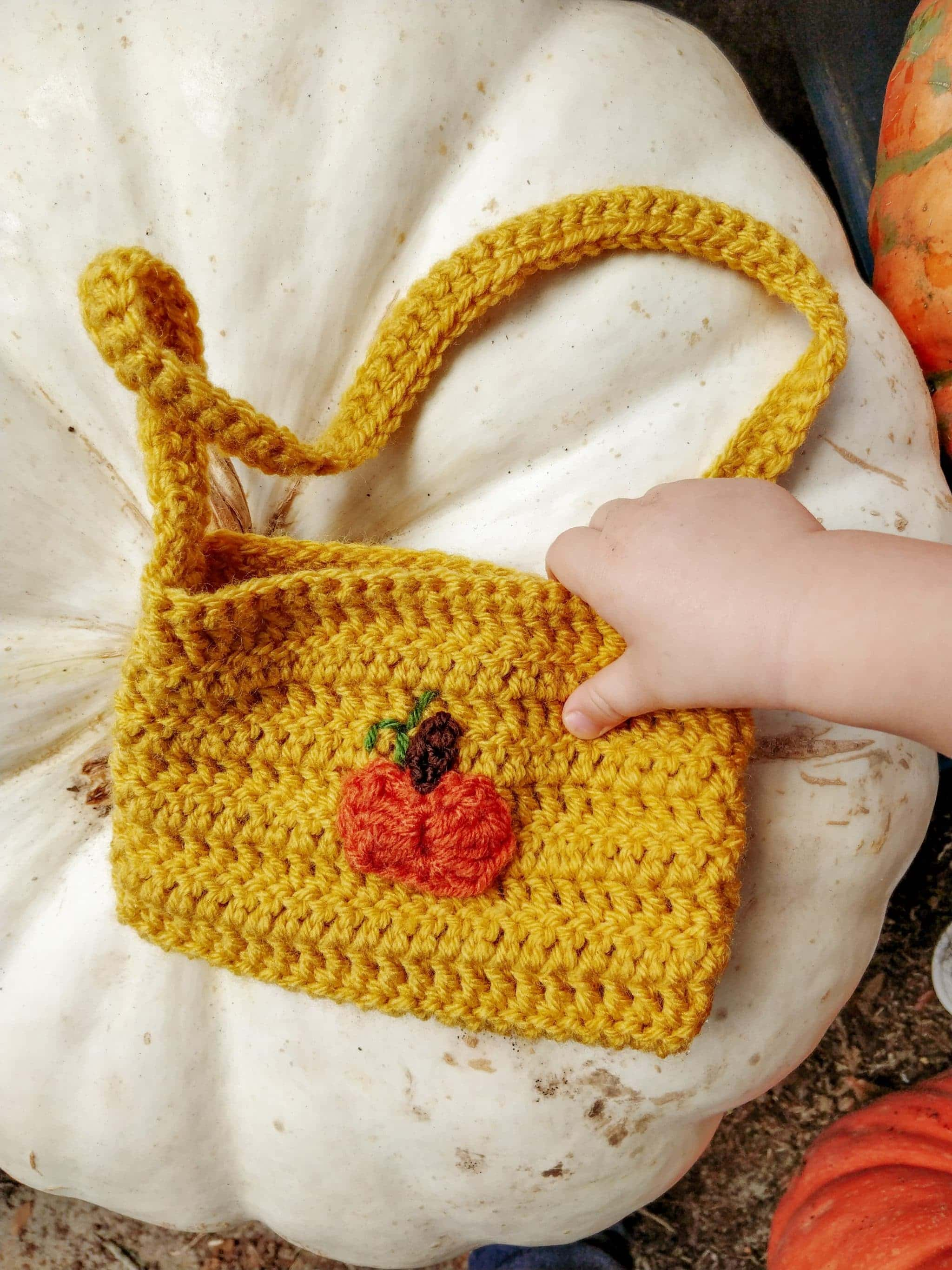 Yellow purse with orange pumpkin embroidered on it