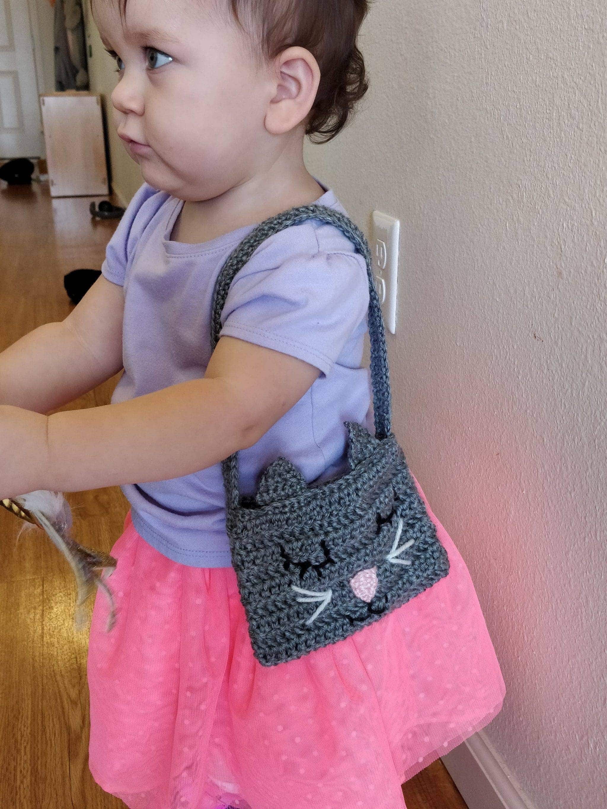 Little girl wearing crochet cat purse on her shoulder while indoors at a house