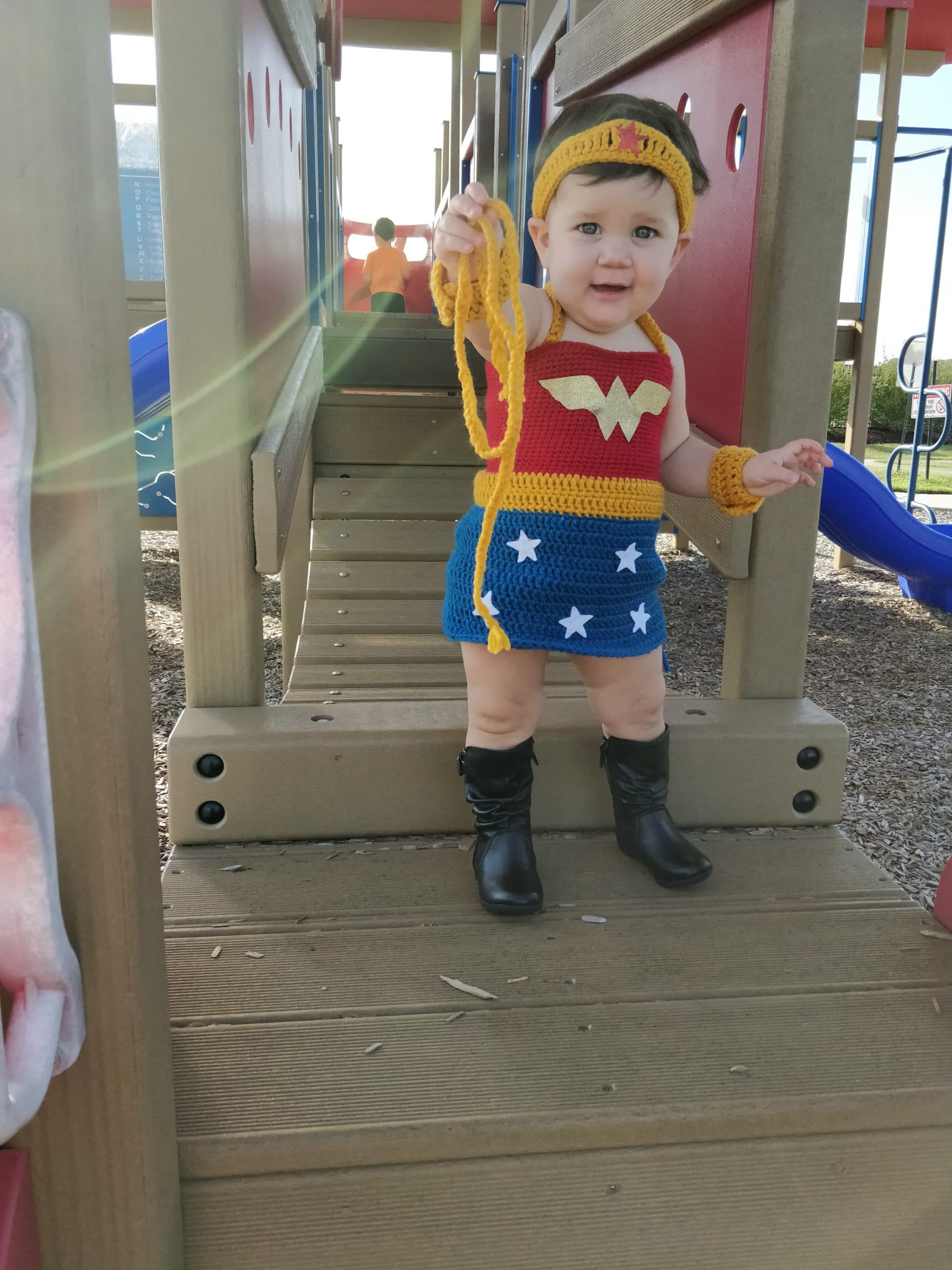 Little girl at the playground wearing wonder woman outfit showing off her lasso of truth