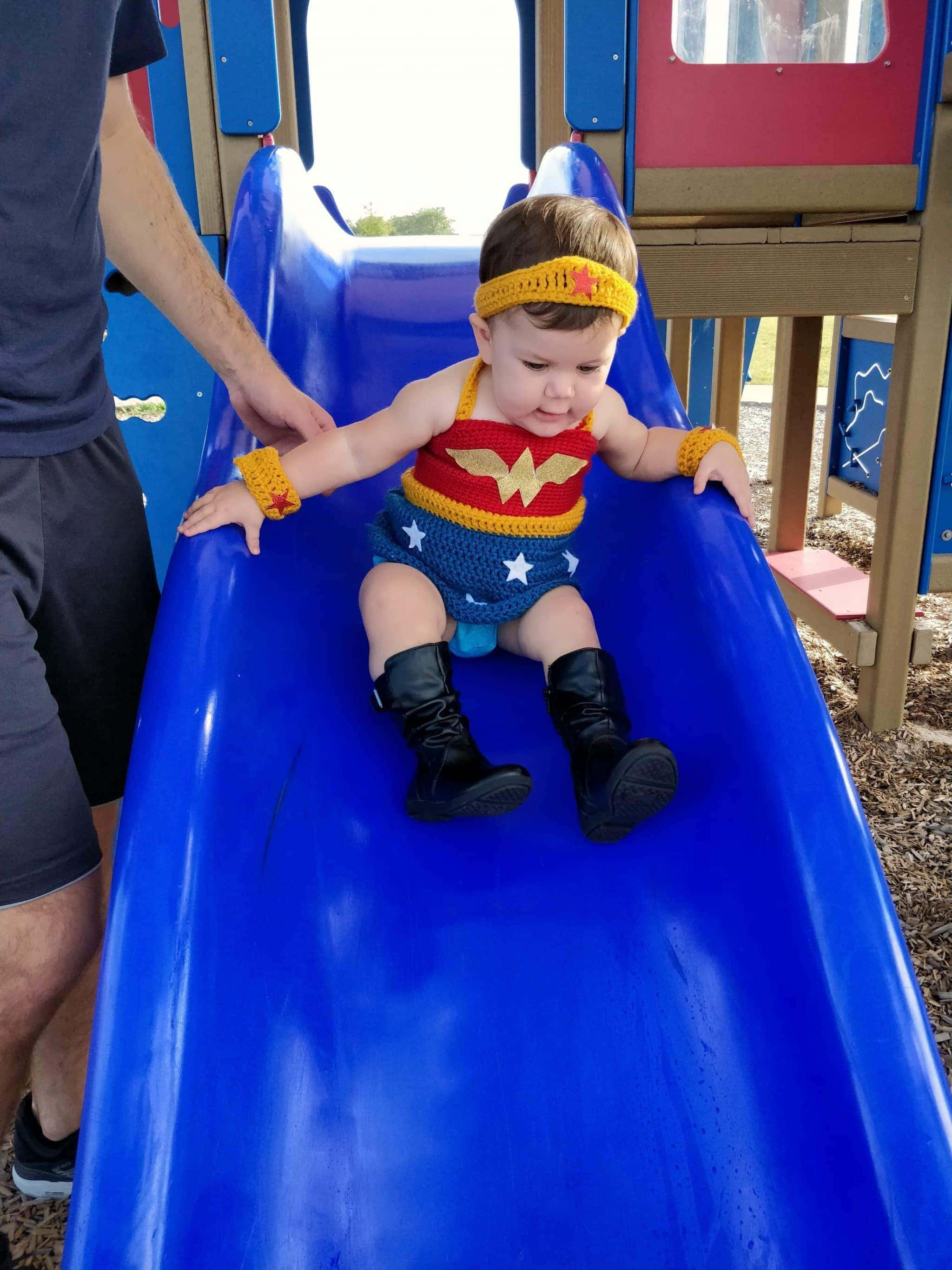 Little girl wearing wonder woman outfit going down a blue slide at the playground