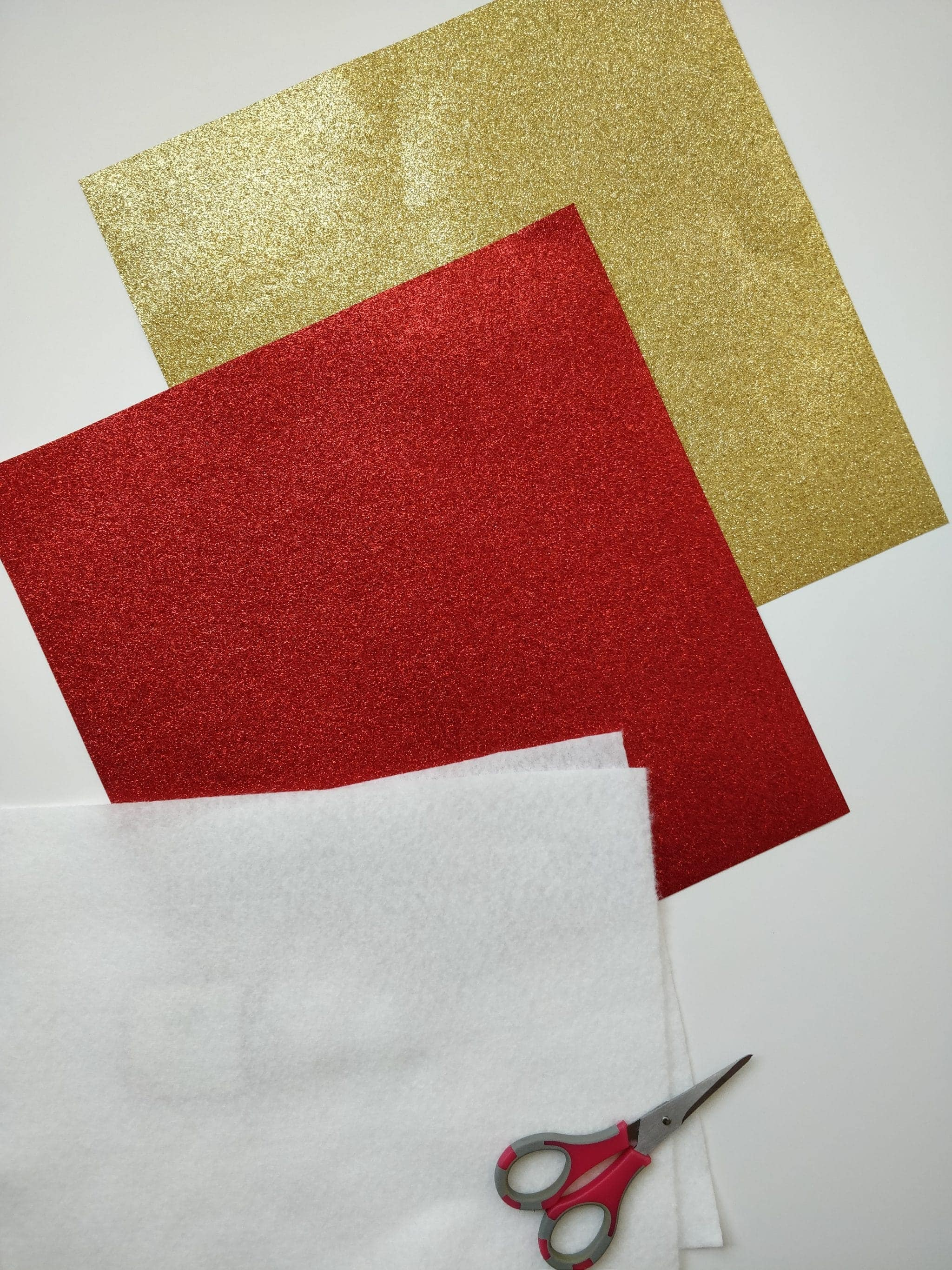 Red and gold glitter paper with scissors and backing material