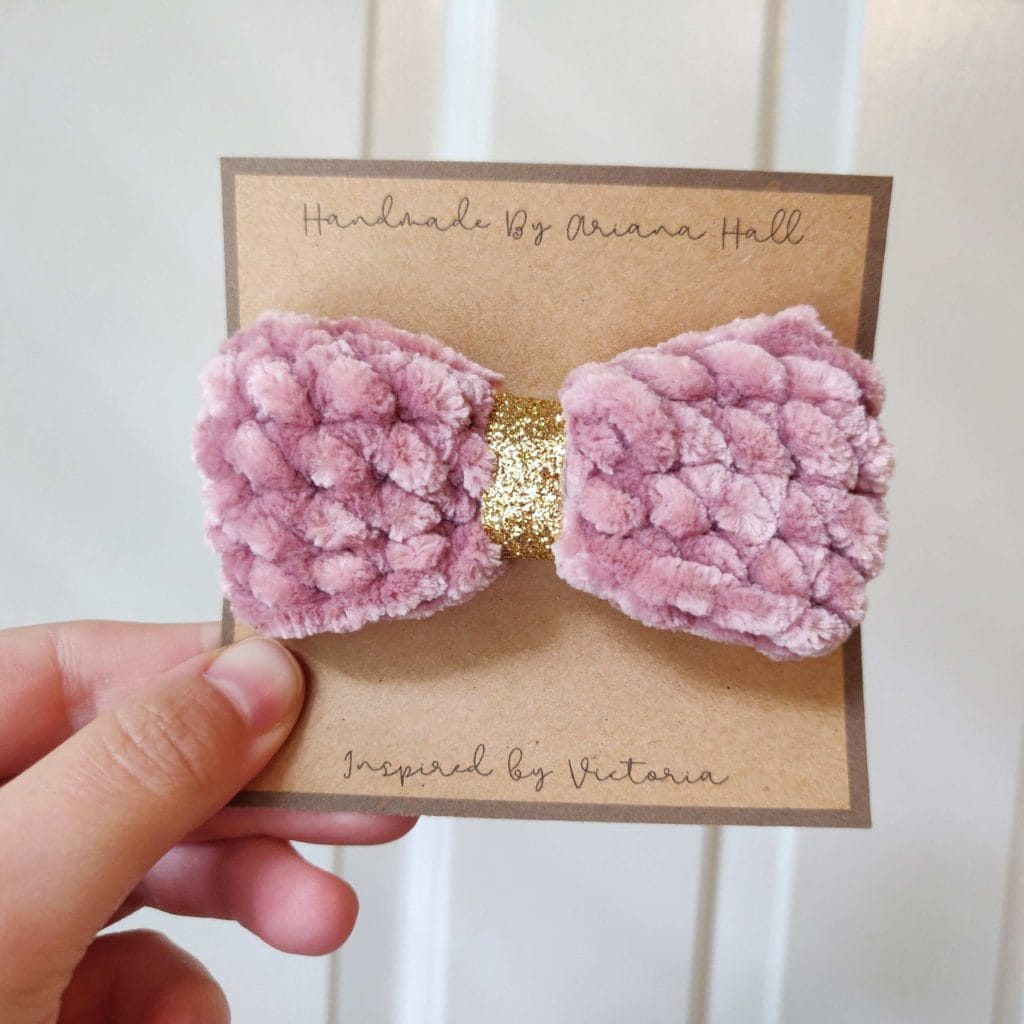 Fuzzy pink cotton bow tied with golden ribbon in the middle