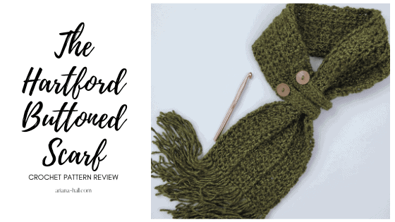 Forest green buttoned scarf and rose gold crochet hook next to it.