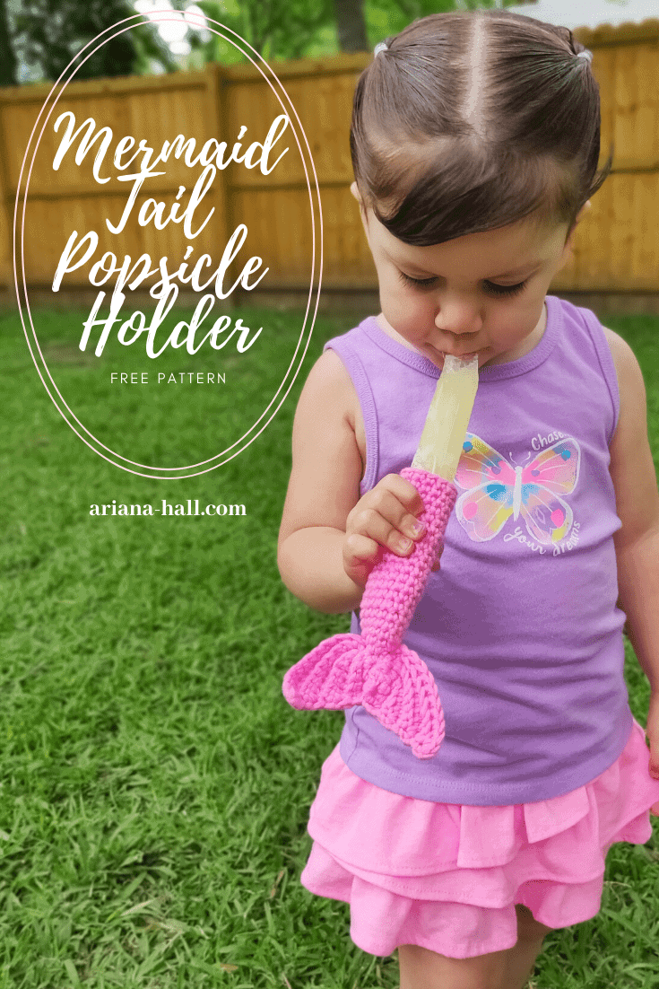 Little girl eating a yellow Popsicle outdoors. The Popsicle is inside a pink crochet mermaid tail holder.