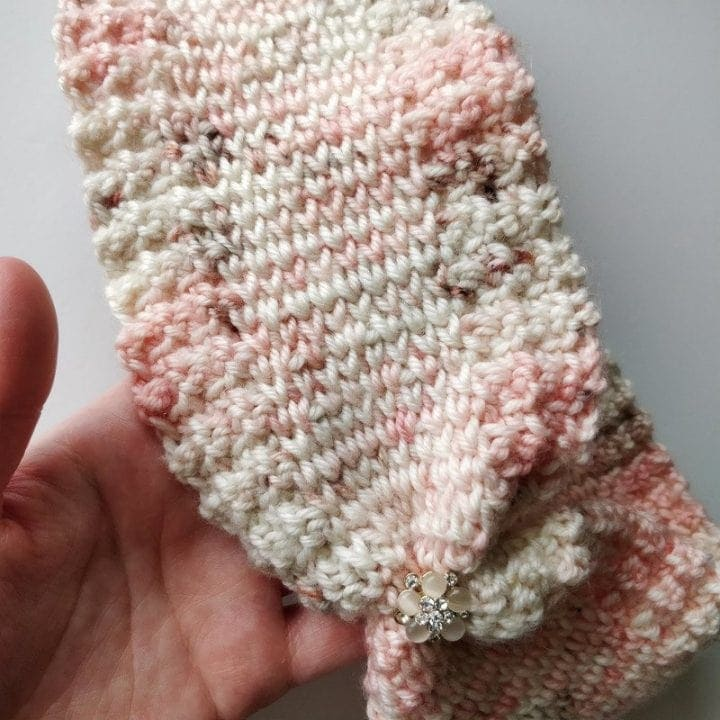 Pink and white and brown close up of finished faux knit ear warmer handmade crochet design using fiber arts