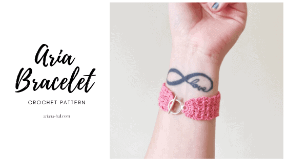 Pink bracelet on a wrist with a tattoo of infinity and says love.