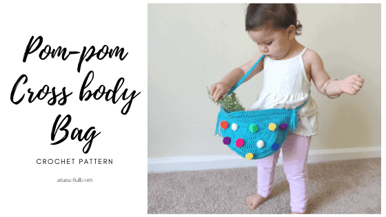 Toddler wearing a cross body bag with colorful pom-poms in the front.