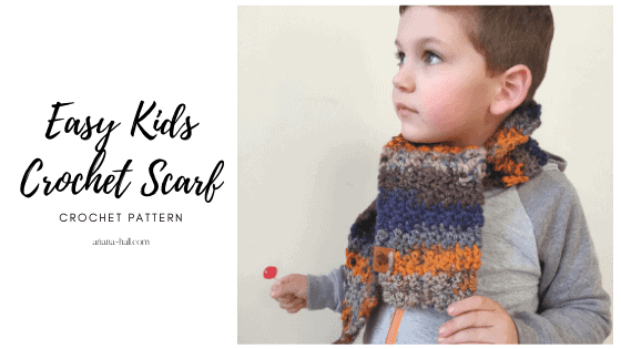 Young boy wearing a kid scarf in brown, orange and blue.