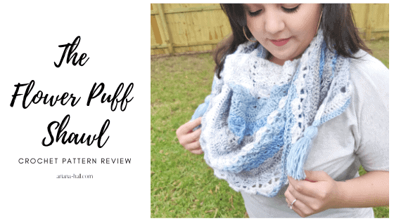 Woman wearing a crochet shawl in the color white, light blue and blue.