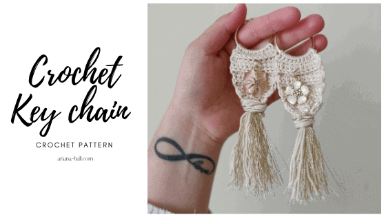 Crochet cream colored key chains with a charm in the center.