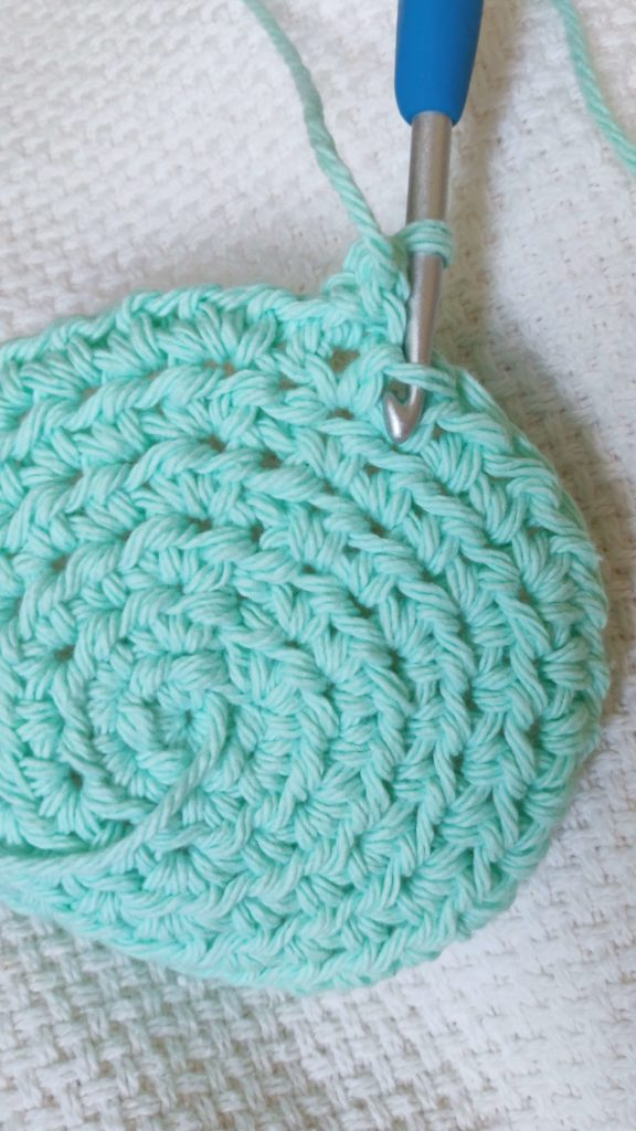 Crochet hook inserted into teal yarn forming the shape of a coaster