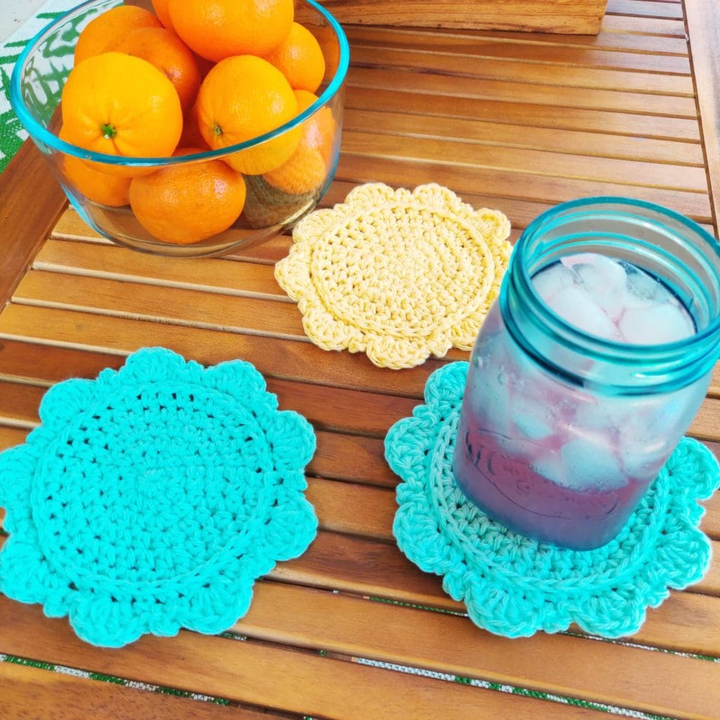 Three yarn crochet coasters on a wooden table with oranges and pink lemonade in a glass jar