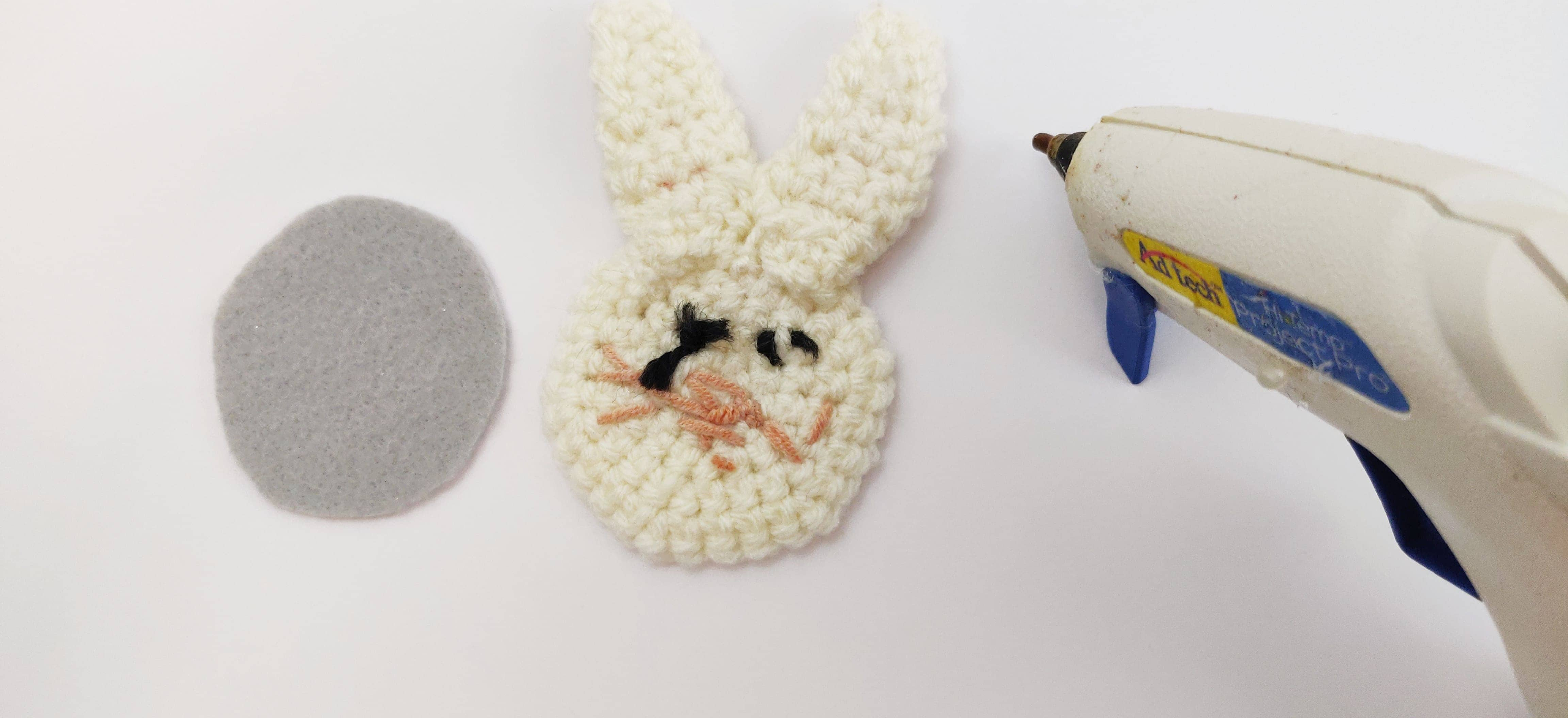 Unassembled crochet bunny applique next to some synthetic backing material and a hot glue gun.