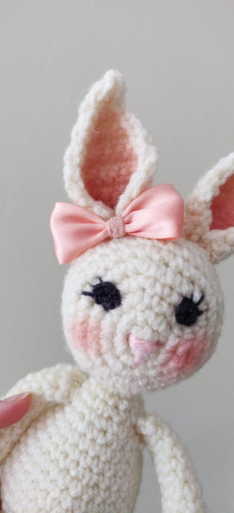 Close up of finished crochet bunny doll face with pink nose and black eyes wearing a pink bow