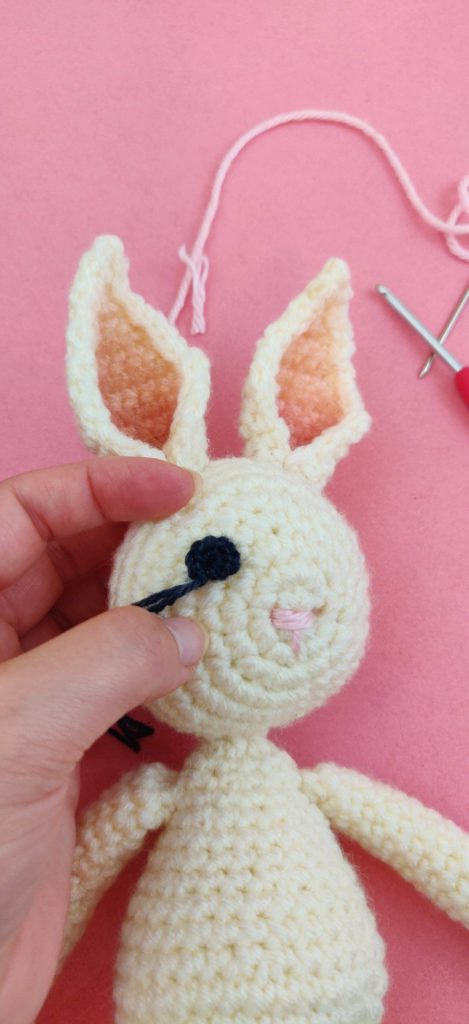 Close up of bunny doll's eyes being stitched