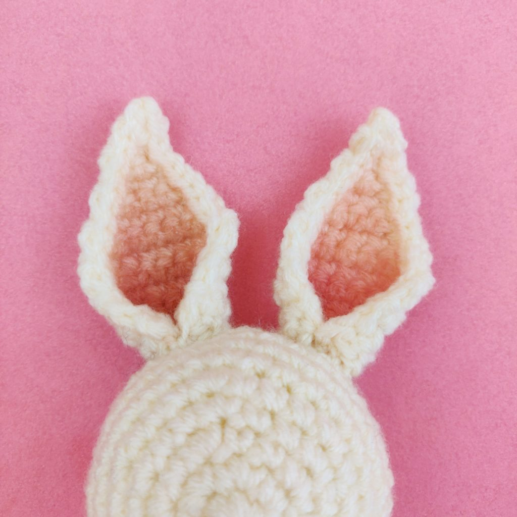 Close up of crochet bunny doll ears being attached to head