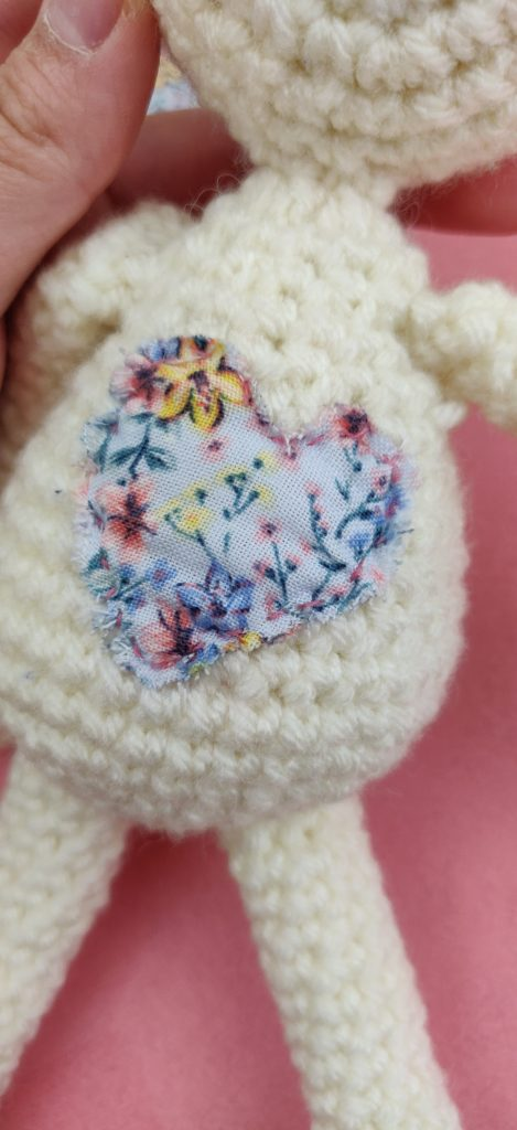 Finished fabric heart attached to crochet bunny doll body