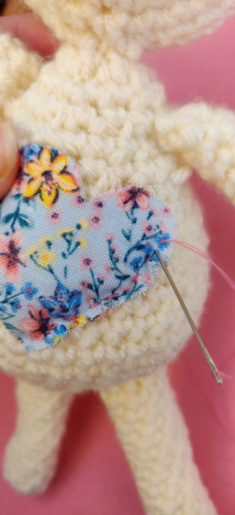Close up of stiching a piece of fabric onto crochet bunny doll body