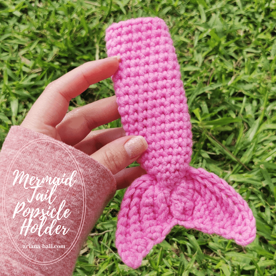 Someone holding a pink crochet mermaid tail Popsicle holder