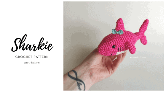 Pink crochet shark with a blue bow on top.