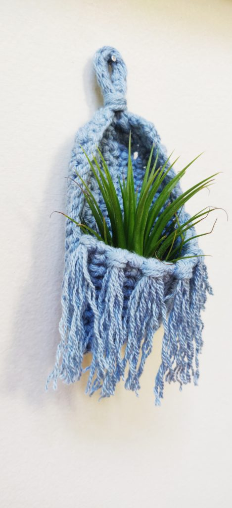 An air plant hanging inside the fringed boho plant holder tacked onto an antique white wall