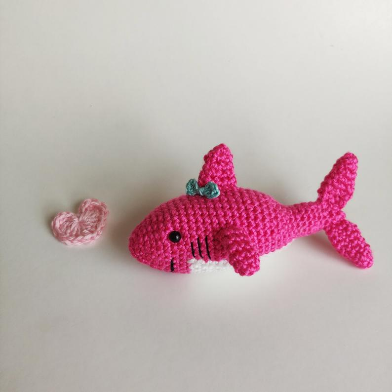 Pink crochet shark with a smile, black circle eyes and turquoise bow on the top fin. Laying next to a pink crochet heart.