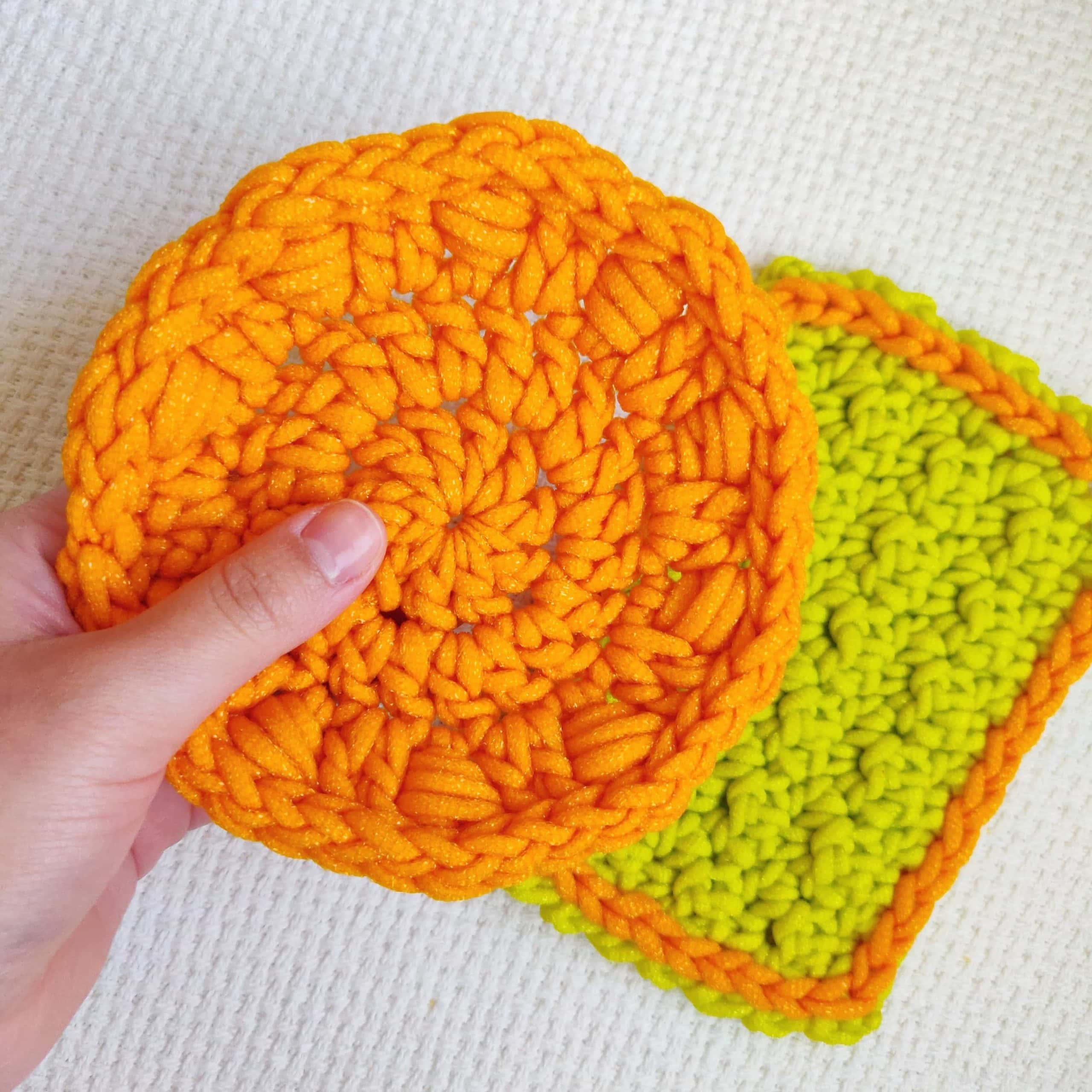 An orange crochet dish scrubby with double crochet and wrap around stitches.