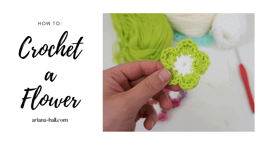 A crochet flower with five green petals and a white center.