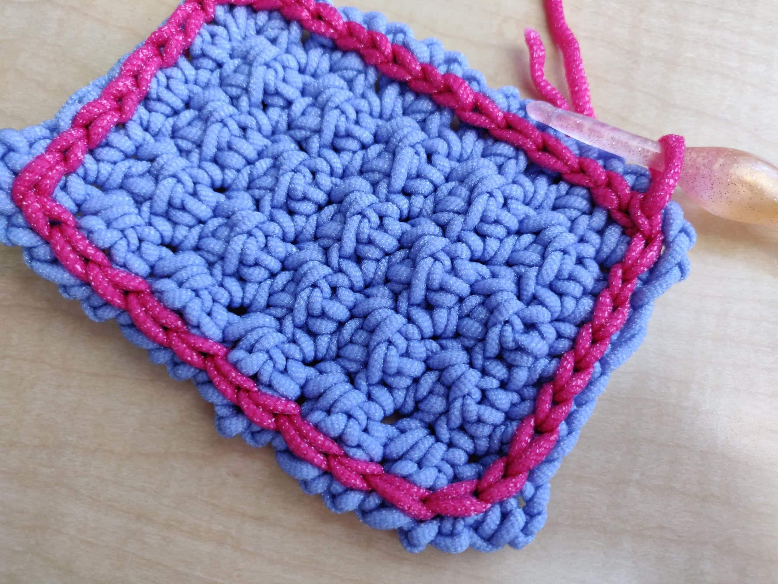 Fastening off a square purple crochet dish scybby with pink yarn and a colorful crochet hook