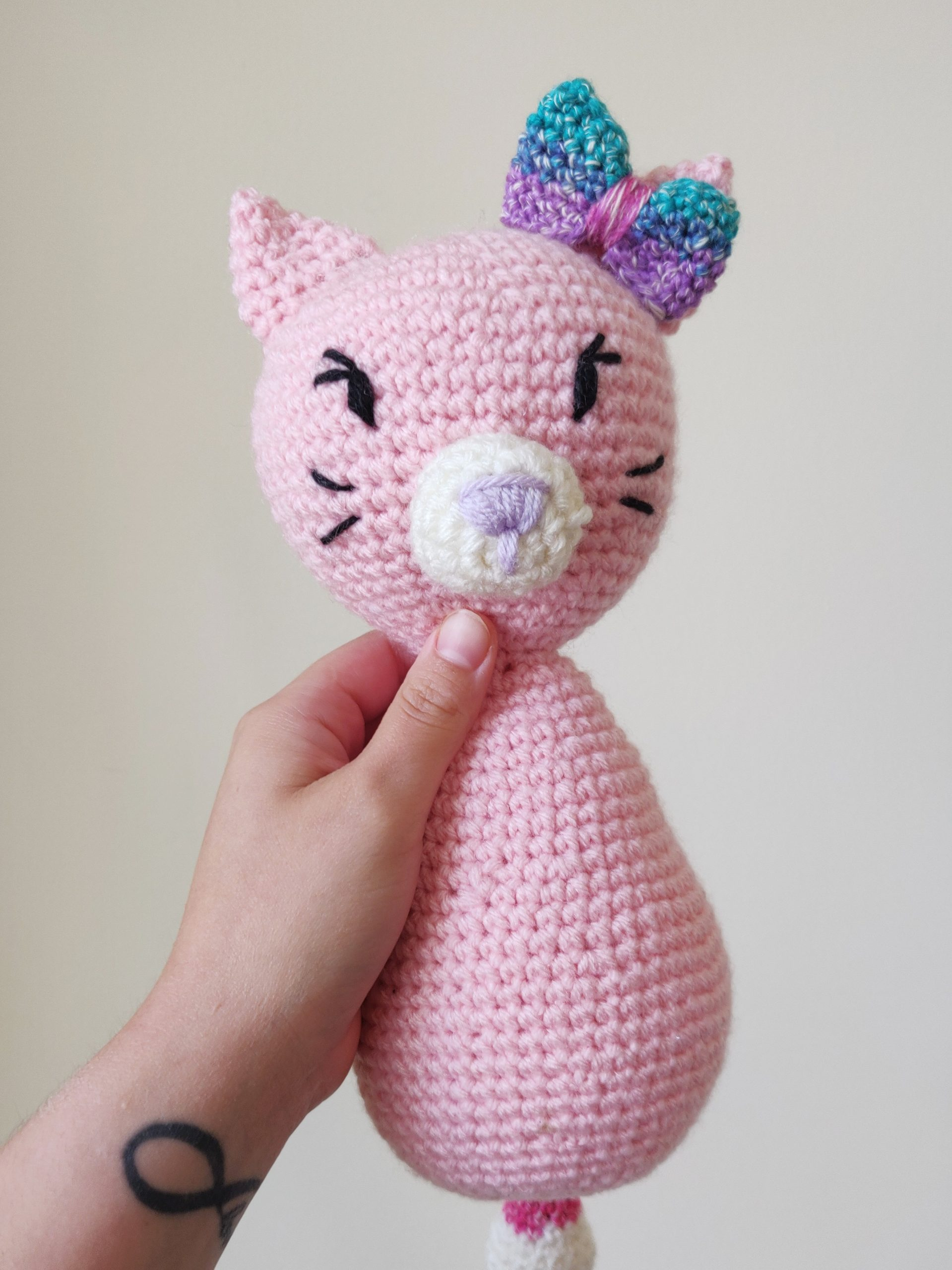 Crochet pink cat with rainbow bow on the right ear.
