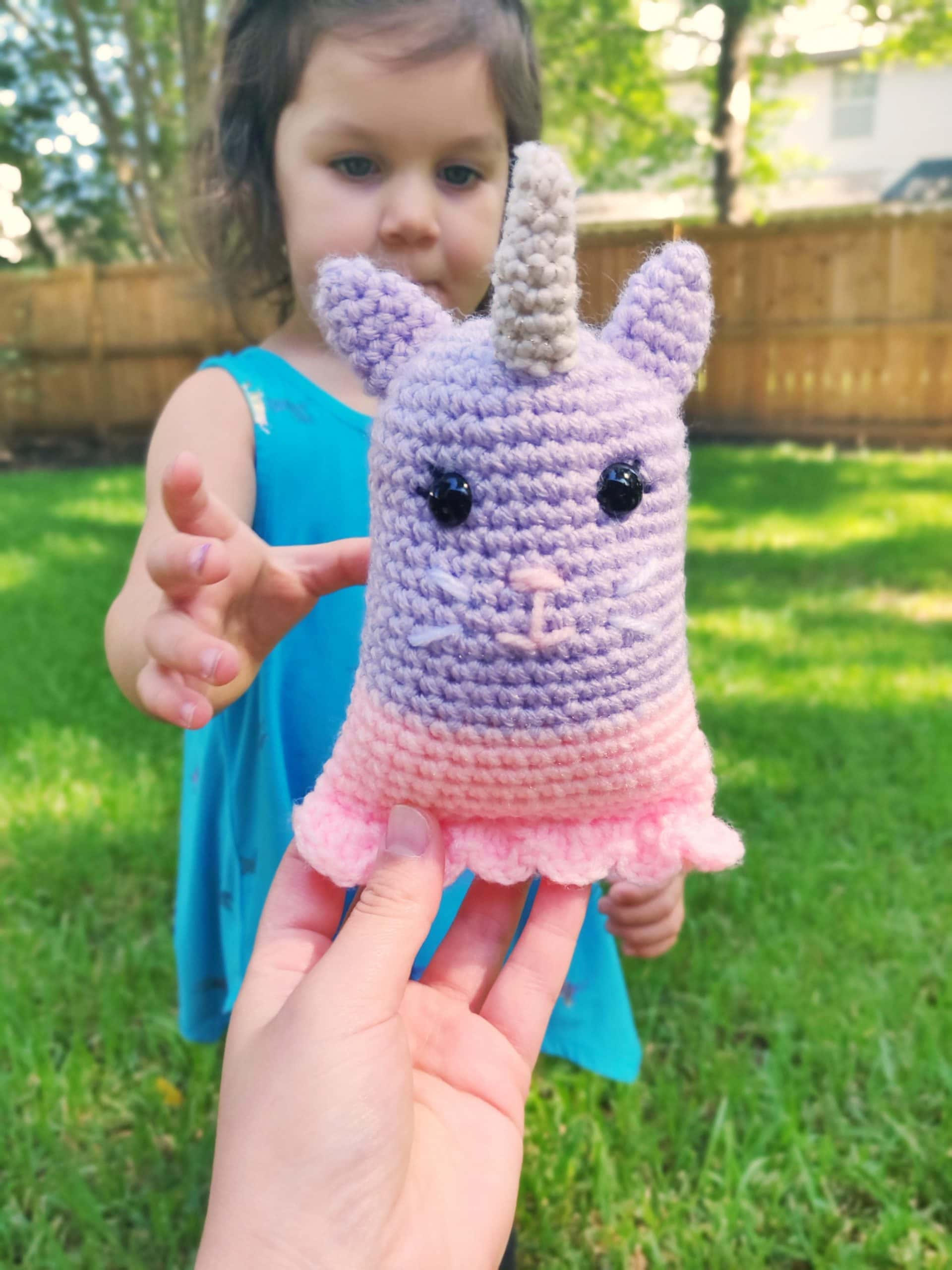 Young girl reaching out for her crochet unicorn kitty toy plush.