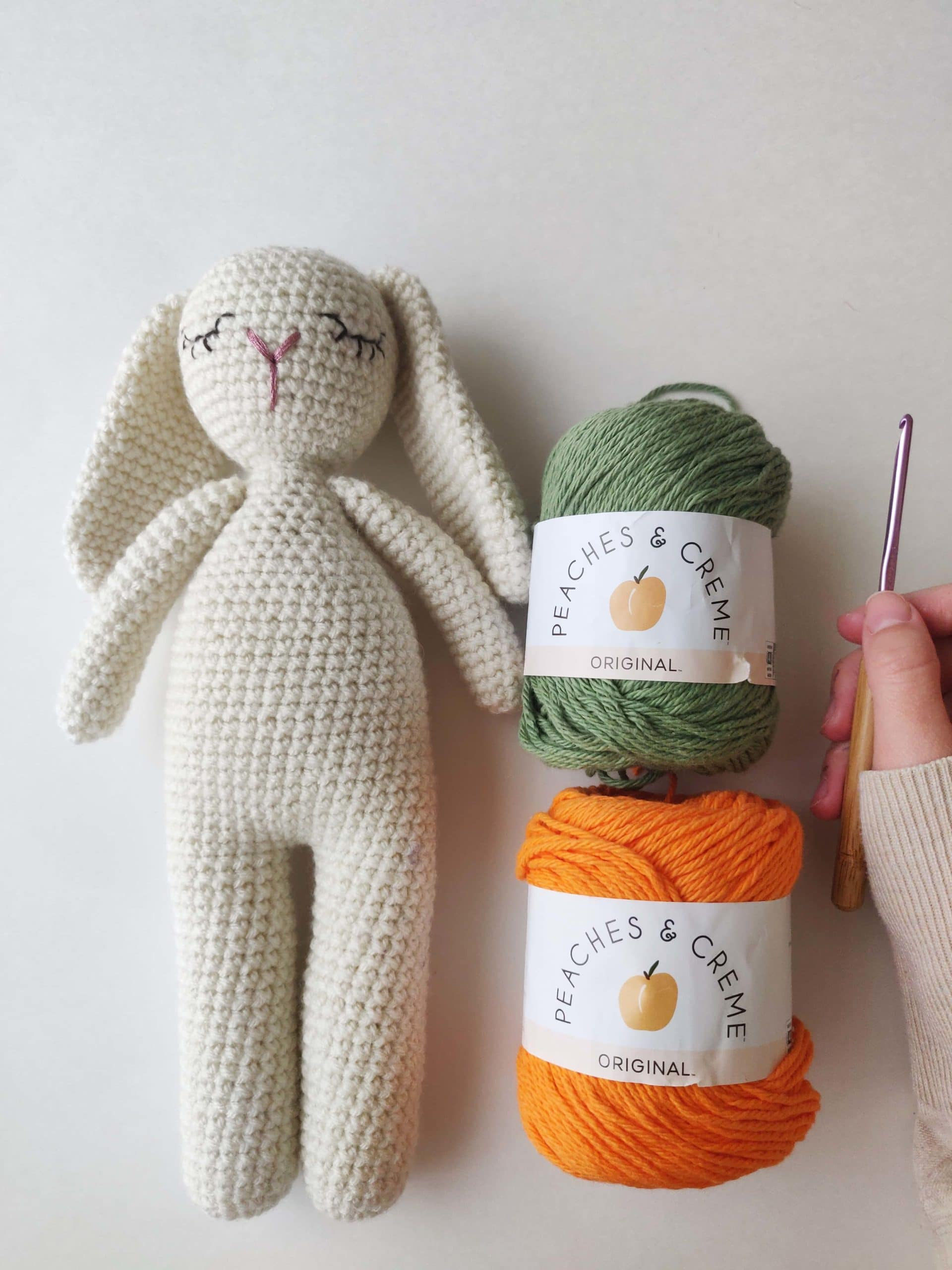 White crochet bunny with orange and green yarn on the right.