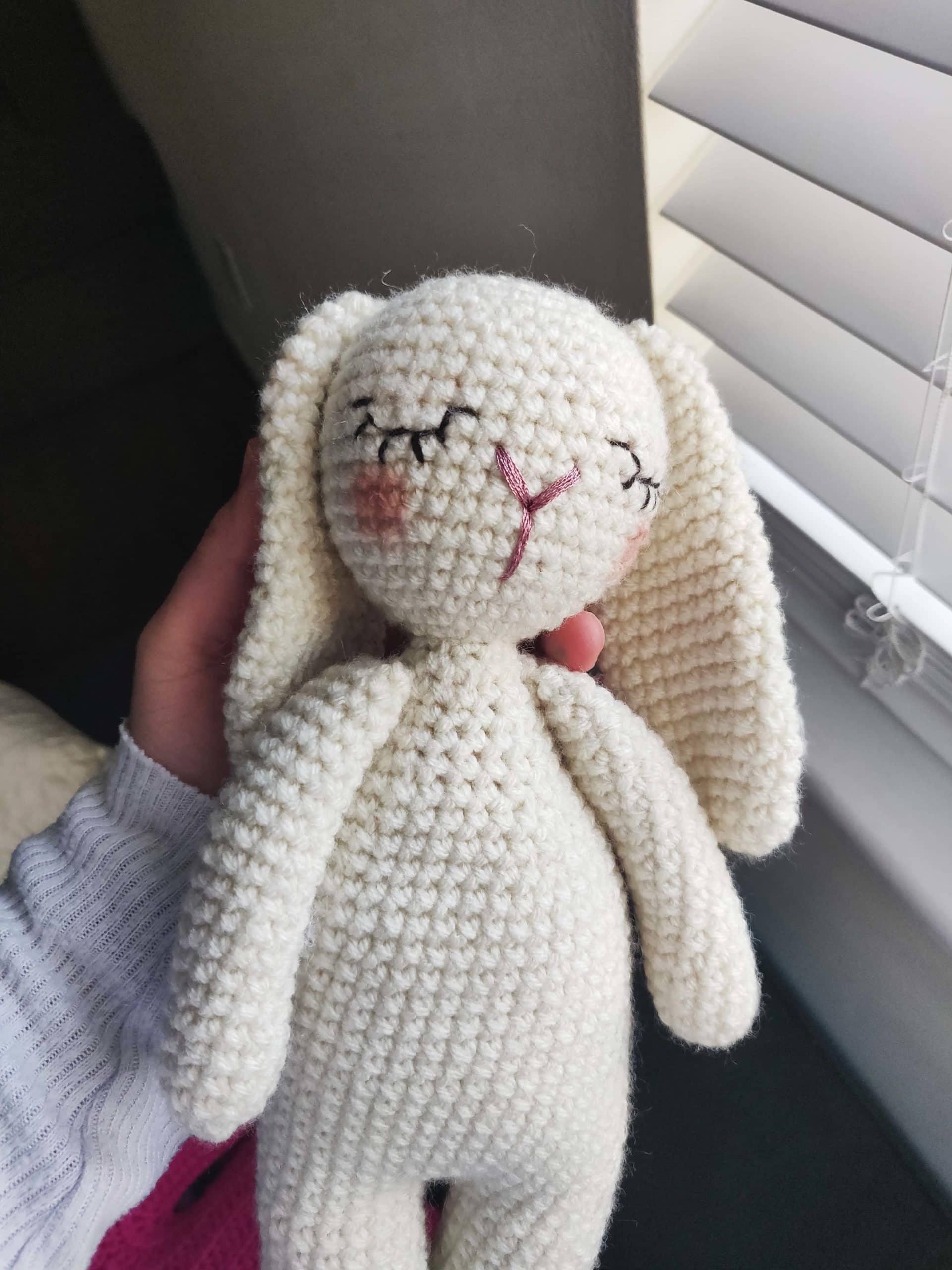 White crochet bunny with pink blush.