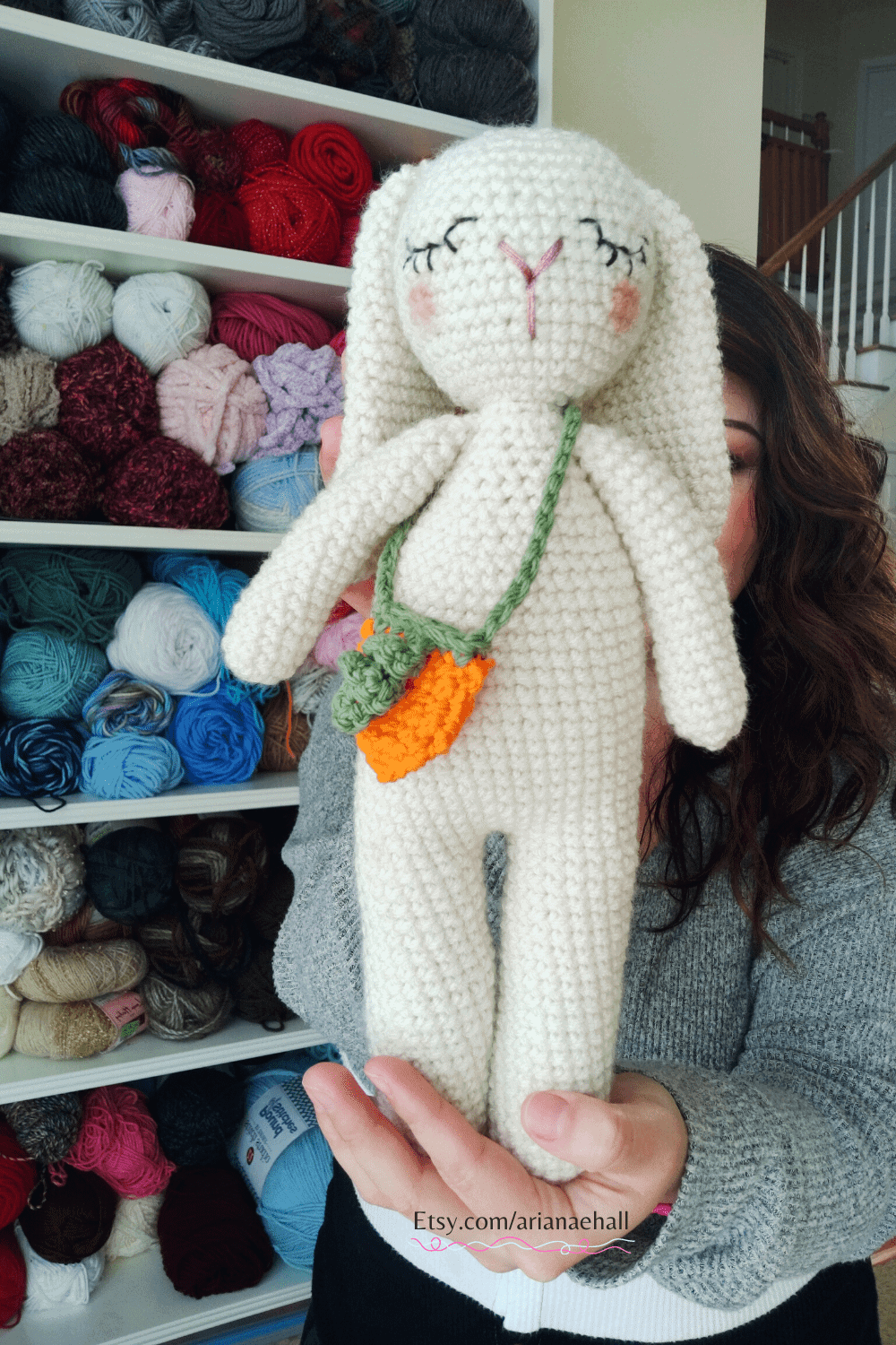 Woman holding white crochet bunny with sleeping eyes to center of camera.
