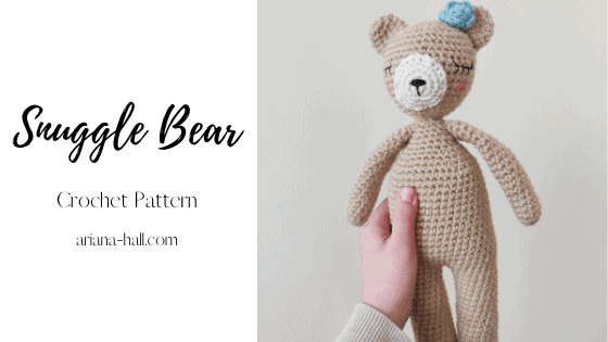 Crochet bear with a blue rose and rosy cheeks