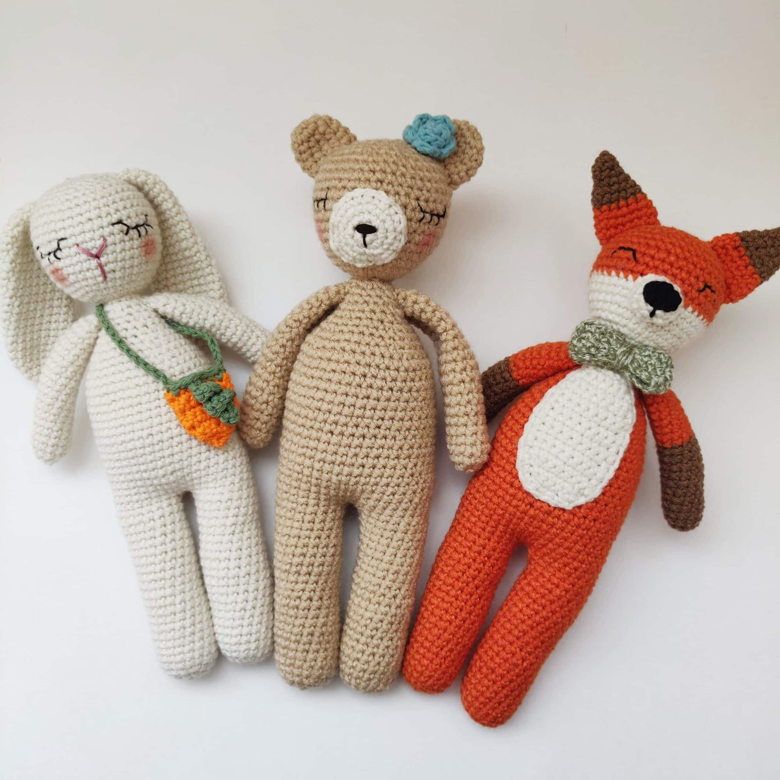 Crochet white rabbit, brown bear and red fox side by side.