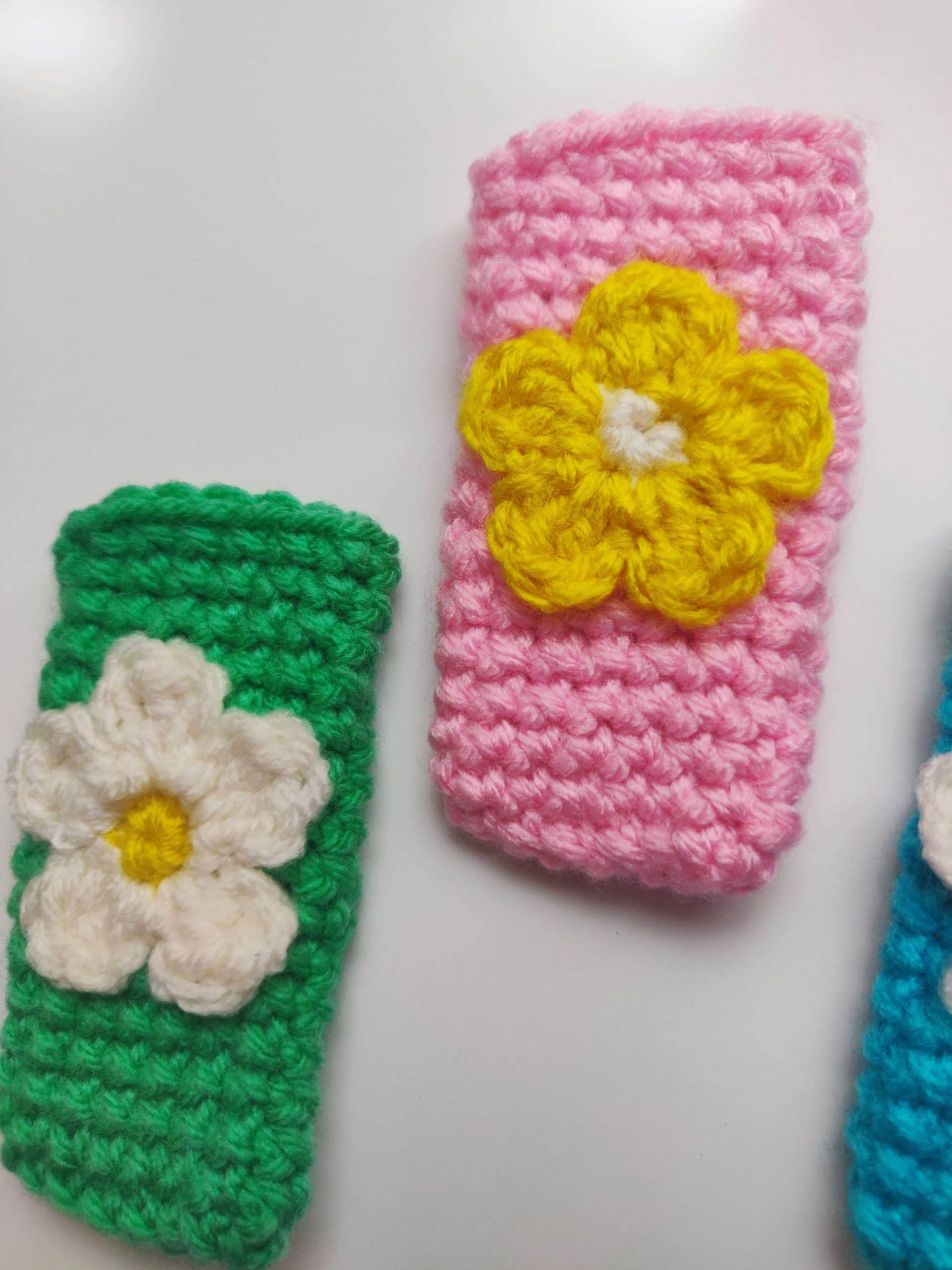 Pink and green crochet popsicle holder with flower in the middle.