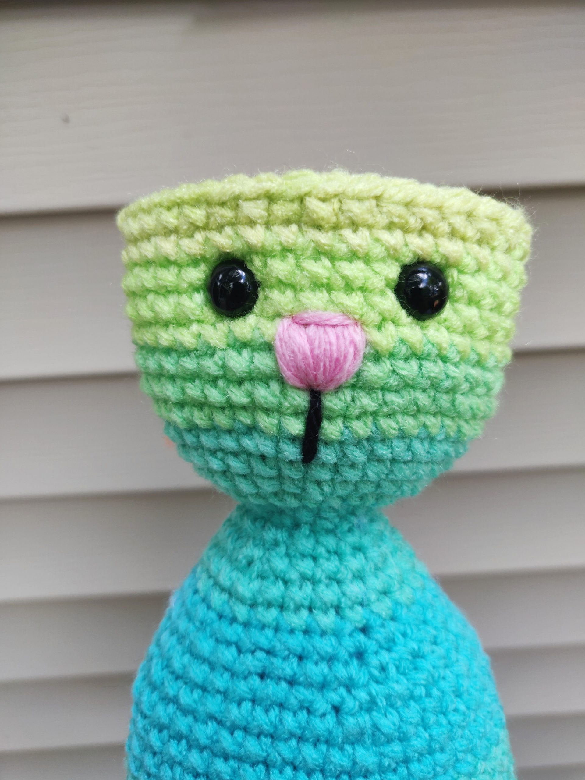 Crochet rainbow yarn, two black safety eyes and pink nose.