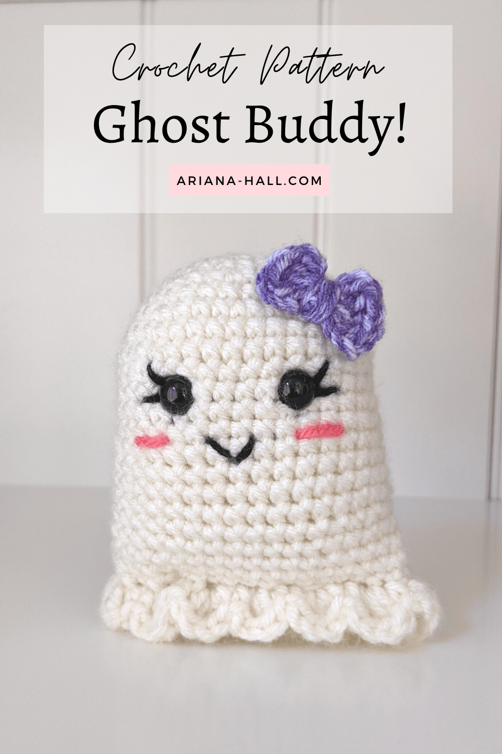 Crochet white ghost smiling with a purple bow.