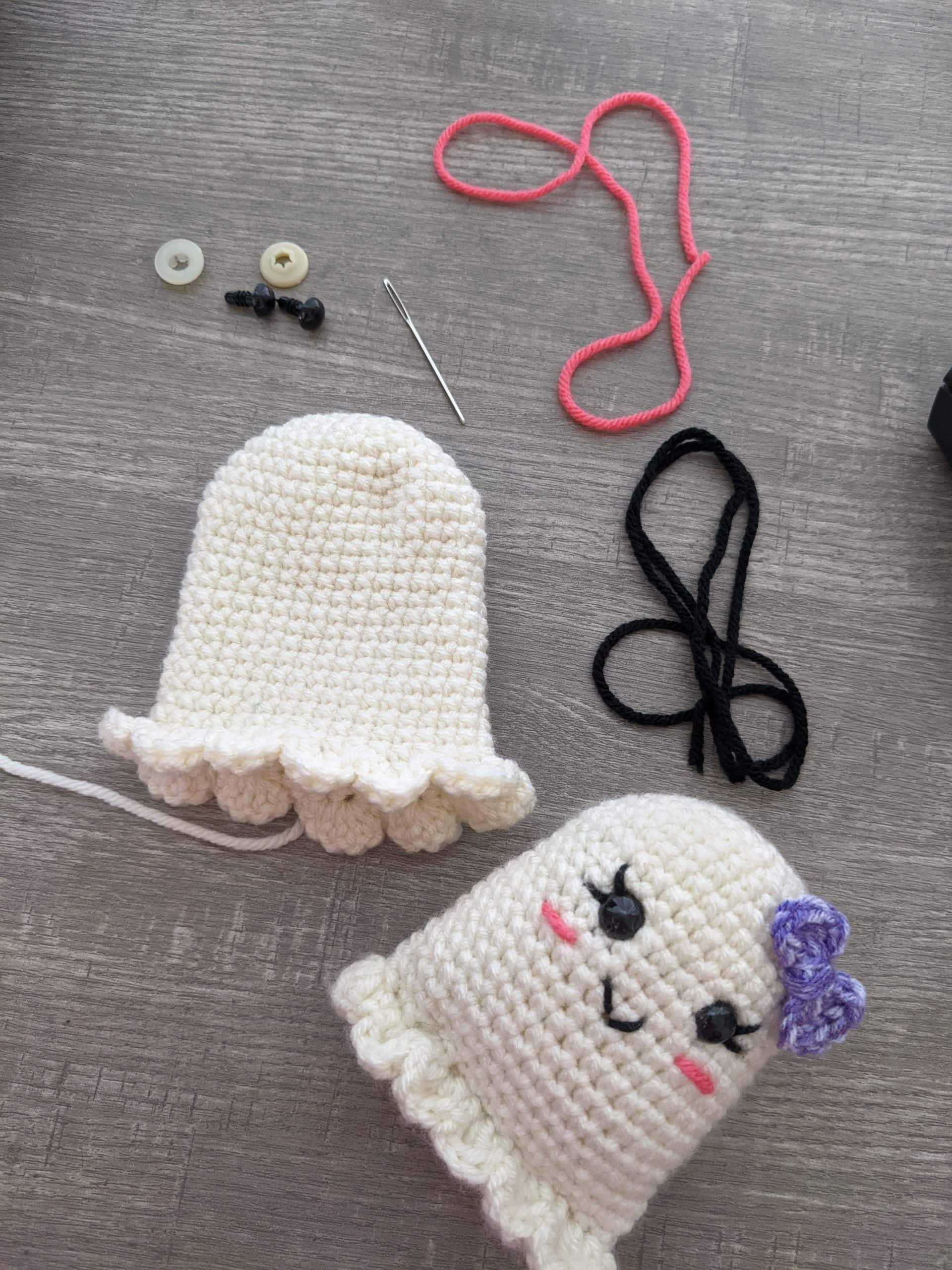 Yarn and crochet white ghost with a purple bow.